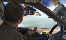 Un policía rompe la ventanilla de un coche