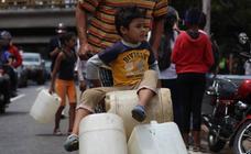Filas para recoger agua debido al apagón, en Caracas