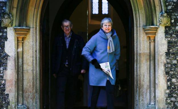 Theresa May y su marido, Philip, salen de la iglesia de Sonning este domingo./REUTERS