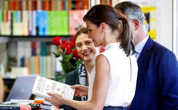 La Reina, con un libro en una de las casetas de la feria.