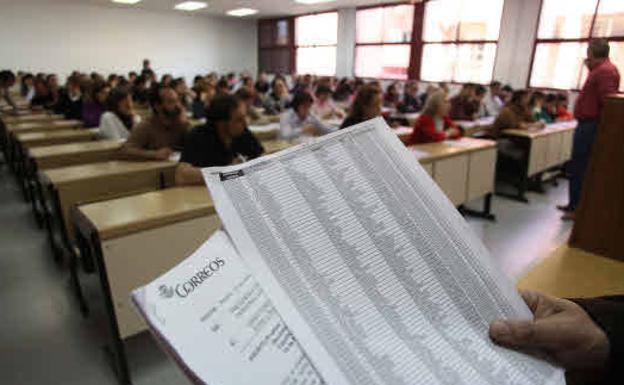 Un grupo de personas, examinándose a las oposiciones de Correos./Archivo