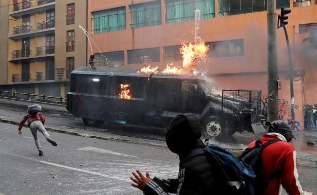 Los manifestantes atacan con bombas incendiarias una tanqueta de la Policía./Reuters