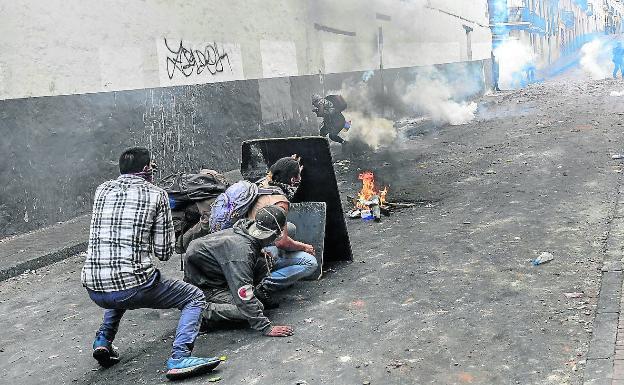 Ecuatorianos que protestan por la supresión de los subsidios a los combustibles se protegen en Quito de los gases lacrimógenos.