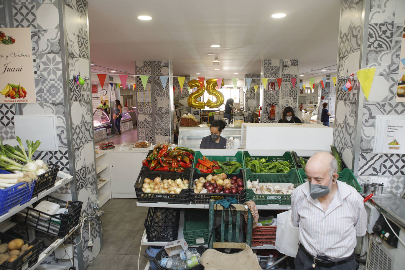 El Mercado Ronda engalanado para la ocasión y, en primer plano, Leandro Galán en el puesto de su hija. /ARMANDO MÉNDEZ