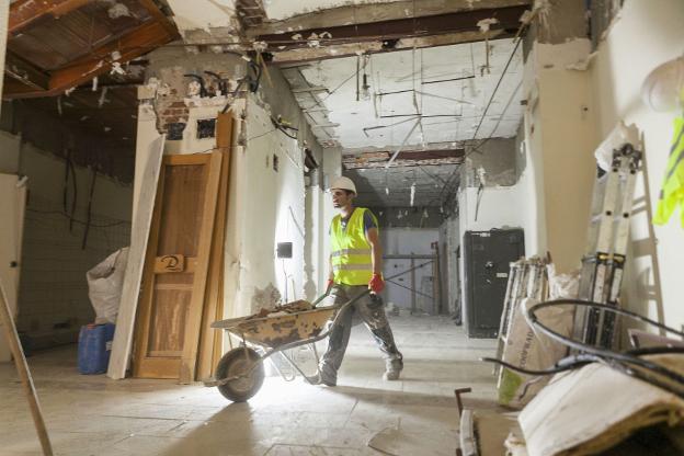 Un albañil carga una carretilla de escombros en un sitio de construcción.  / HOY